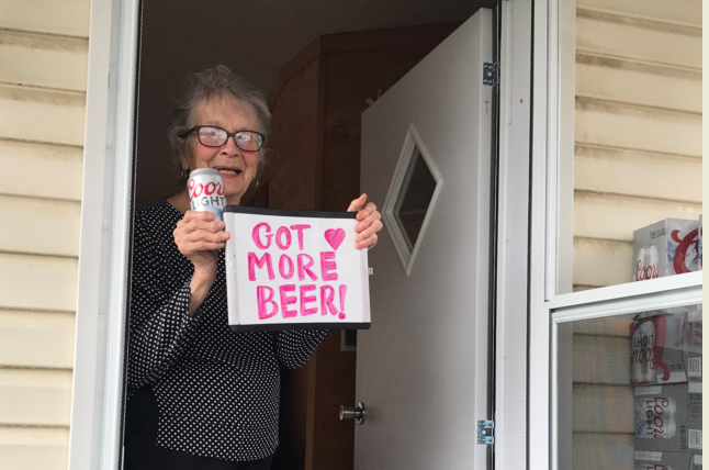"Olive Veronesi celebrates getting a stash of Coors Light with a sign that says, ""Got More Beer!"""